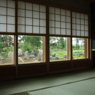Ejemplo de habitación de invitados de estilo americano, grande, sin chimenea, con paredes negras, tatami y suelo verde