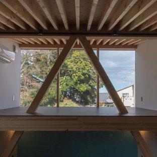 Свежая идея для дизайна: спальня среднего размера на антресоли в восточном стиле с синими стенами, татами, печью-буржуйкой, фасадом камина из бетона и бежевым полом - отличное фото интерьера
