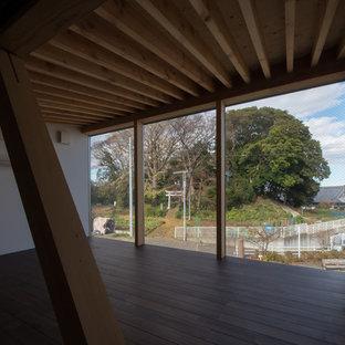 Foto de dormitorio tipo loft, de estilo zen, de tamaño medio, con paredes blancas, suelo de madera oscura, estufa de leña, marco de chimenea de hormigón y suelo marrón