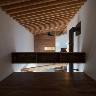 Diseño de dormitorio tipo loft, de estilo zen, de tamaño medio, con paredes blancas, suelo de madera oscura, estufa de leña, marco de chimenea de hormigón y suelo marrón