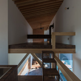 Imagen de dormitorio tipo loft, asiático, de tamaño medio, con paredes blancas, suelo de madera oscura, estufa de leña, marco de chimenea de hormigón y suelo marrón