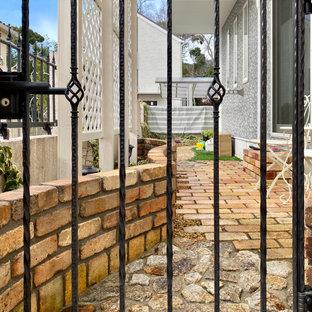 Esempio di un piccolo giardino country esposto in pieno sole nel cortile laterale in inverno con pavimentazioni in mattoni