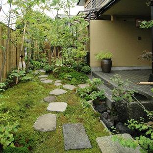 Inspiration för en mellanstor orientalisk formell trädgård i full sol framför huset på sommaren, med en trädgårdsgång och naturstensplattor
