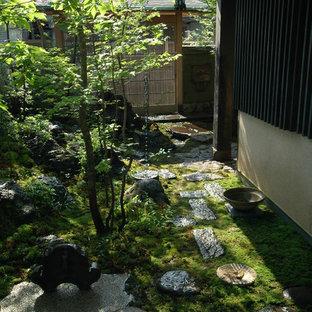 Idéer för att renovera en mellanstor orientalisk formell trädgård i delvis sol framför huset på sommaren, med naturstensplattor