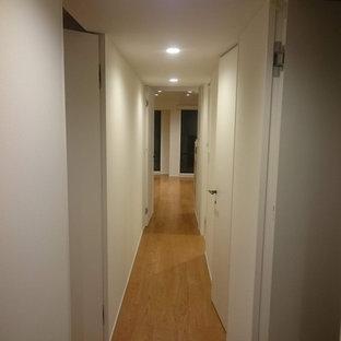Cette image montre un couloir minimaliste de taille moyenne avec un sol en bois brun, un sol beige, un plafond en papier peint et du papier peint.