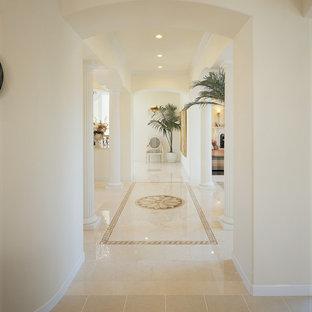 他の地域の巨大な地中海スタイルのおしゃれな廊下 (白い壁、大理石の床、ベージュの床) の写真