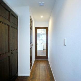 Foto på en liten skandinavisk hall, med vita väggar, plywoodgolv och brunt golv