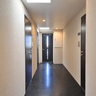 Example of a small trendy linoleum floor and black floor hallway design in Tokyo with white walls