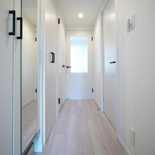 Inspiration för en nordisk hall, med vita väggar, plywoodgolv och beiget golv