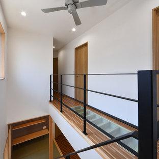 Cette image montre un petit couloir design avec un mur blanc, un sol en contreplaqué et un sol marron.