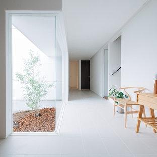他の地域のモダンスタイルのおしゃれな廊下 (白い壁、磁器タイルの床、白い床) の写真