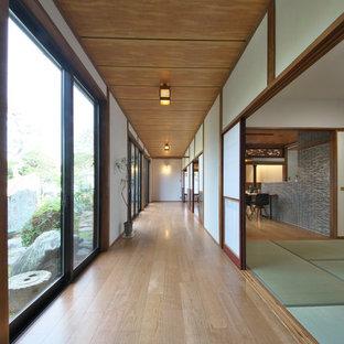 Inspiration för asiatiska hallar, med vita väggar, mellanmörkt trägolv och brunt golv