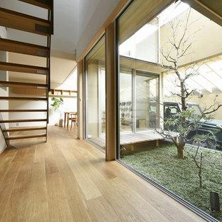 京都のアジアンスタイルのおしゃれな廊下 (白い壁、淡色無垢フローリング、茶色い床) の写真