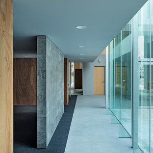 Inspiration pour un très grand couloir minimaliste avec un mur gris, béton au sol, un sol gris, un plafond en papier peint et du lambris.