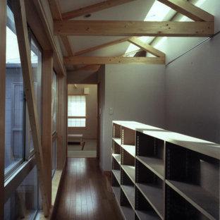 Modern inredning av en liten hall, med beige väggar, mellanmörkt trägolv och brunt golv