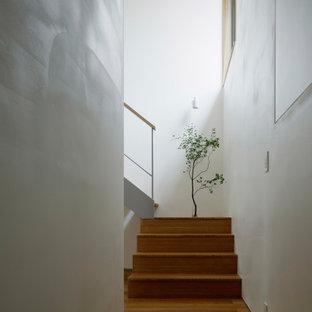 Inspiration pour un couloir minimaliste de taille moyenne avec un mur blanc, un sol en contreplaqué et un sol marron.