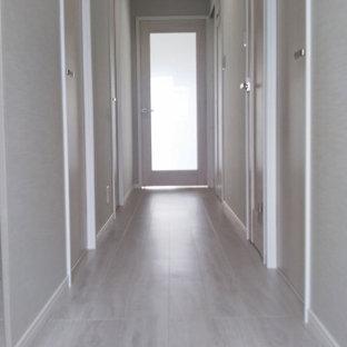 他の地域の小さいモダンスタイルのおしゃれな廊下 (グレーの壁、合板フローリング、白い床、クロスの天井、壁紙) の写真