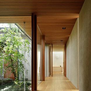 他の地域のアジアンスタイルのおしゃれな廊下 (グレーの壁、淡色無垢フローリング、茶色い床) の写真