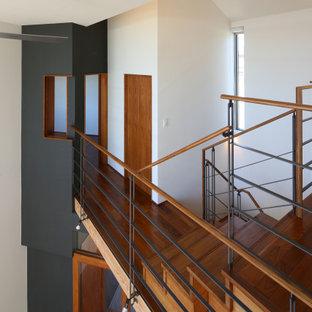 Bild på en funkis hall, med vita väggar, mellanmörkt trägolv och brunt golv