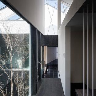 他の地域のコンテンポラリースタイルのおしゃれな廊下 (白い壁、塗装フローリング、黒い床) の写真