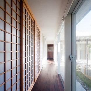 他の地域のコンテンポラリースタイルのおしゃれな廊下 (濃色無垢フローリング、茶色い床) の写真