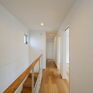 他の地域の北欧スタイルのおしゃれな廊下 (白い壁、無垢フローリング、茶色い床) の写真