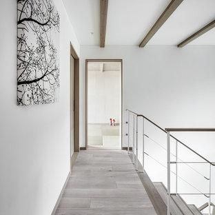 На фото: коридор в стиле модернизм с белыми стенами, деревянным полом и серым полом с