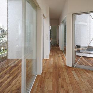 他の地域のコンテンポラリースタイルのおしゃれな廊下 (白い壁、無垢フローリング、茶色い床) の写真