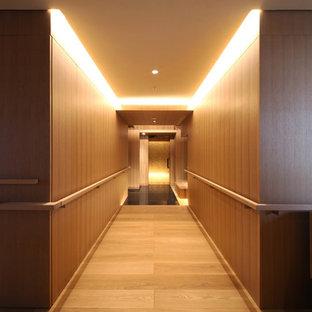 Réalisation d'un grand couloir minimaliste avec un mur marron, un sol en contreplaqué et un sol marron.