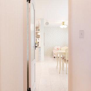 Shabby chic-inspirerad inredning av en liten hall, med vita väggar, plywoodgolv och vitt golv