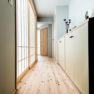 和風のおしゃれな廊下 (青い壁、無垢フローリング、茶色い床) の写真