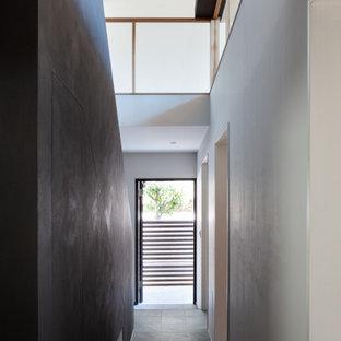 Cette image montre un couloir avec un mur blanc, un sol en ardoise, un sol gris, un plafond en lambris de bois et du lambris de bois.