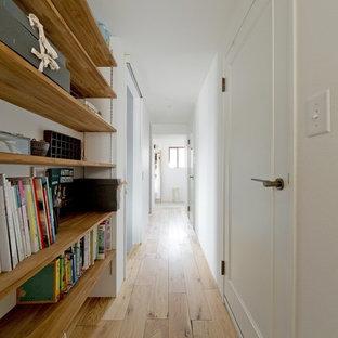 Cette image montre un couloir nordique avec un mur blanc, un sol beige et un sol en bois clair.