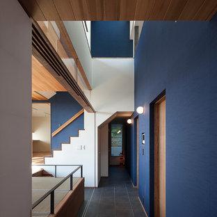 東京23区のアジアンスタイルのおしゃれな廊下 (青い壁、黒い床) の写真