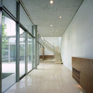 他の地域の大きいモダンスタイルのおしゃれな廊下 (ベージュの壁、大理石の床、ベージュの床) の写真