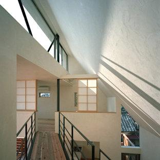 Inredning av en modern hall, med vita väggar, mellanmörkt trägolv och brunt golv