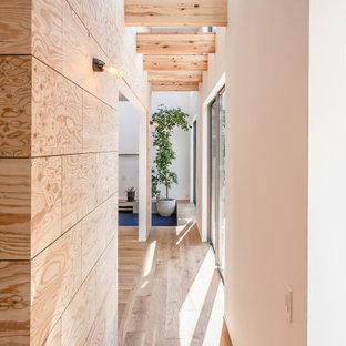 Modern inredning av en hall, med vita väggar och ljust trägolv