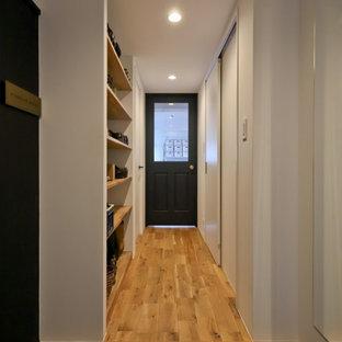 Idéer för små funkis hallar, med vita väggar, mellanmörkt trägolv och beiget golv