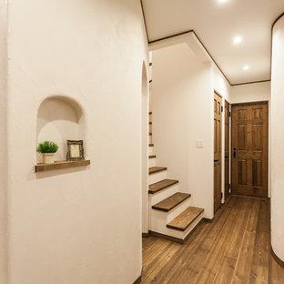 名古屋の地中海スタイルのおしゃれな廊下 (ベージュの壁、茶色い床) の写真