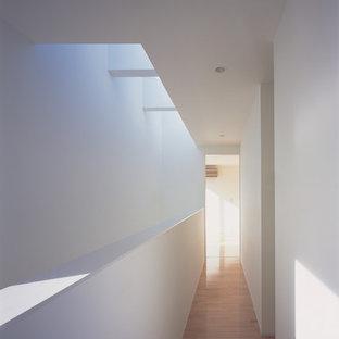 Diseño de recibidores y pasillos minimalistas, de tamaño medio, con paredes blancas, suelo de madera en tonos medios y suelo rosa