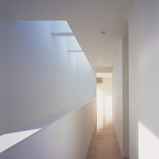 На фото: коридор среднего размера в стиле модернизм с белыми стенами, паркетным полом среднего тона и розовым полом