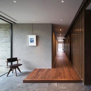 Выдающиеся фото от архитекторов и дизайнеров интерьера: большой коридор в стиле модернизм с серыми стенами, темным паркетным полом и коричневым полом