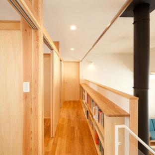 Foto på en mellanstor funkis hall, med vita väggar och mellanmörkt trägolv