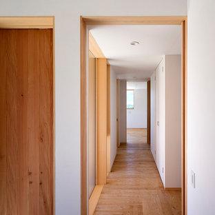 他の地域の小さい北欧スタイルのおしゃれな廊下 (黒い壁、無垢フローリング) の写真