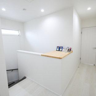 他の地域の中くらいのモダンスタイルのおしゃれな廊下 (白い壁、合板フローリング、白い床) の写真