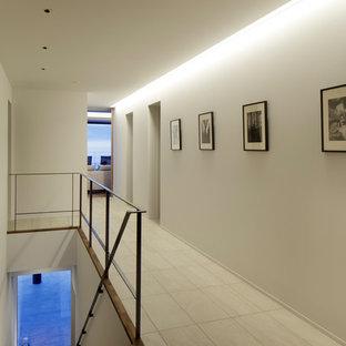 他の地域の中くらいのモダンスタイルのおしゃれな廊下 (白い壁、ベージュの床) の写真