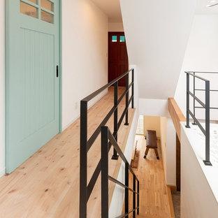 Midcentury hallway in Kyoto with white walls, light hardwood floors and beige floor.