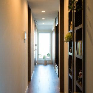 東京23区の中くらいの北欧スタイルのおしゃれな廊下 (ベージュの壁、合板フローリング、茶色い床) の写真