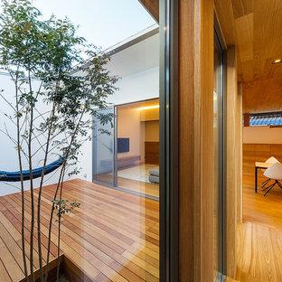 Inspiration pour un couloir minimaliste de taille moyenne avec un mur blanc, un sol marron et un sol en contreplaqué.