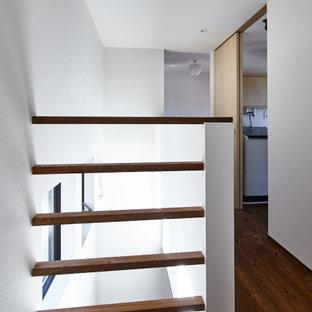 Idées déco pour un couloir contemporain de taille moyenne avec un mur blanc, un sol en bois brun, un sol marron, un plafond en lambris de bois et du lambris de bois.
